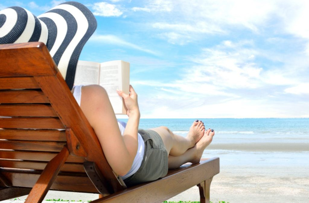 Woman reading on the beach after winning an all summer long beach reads giveaway.