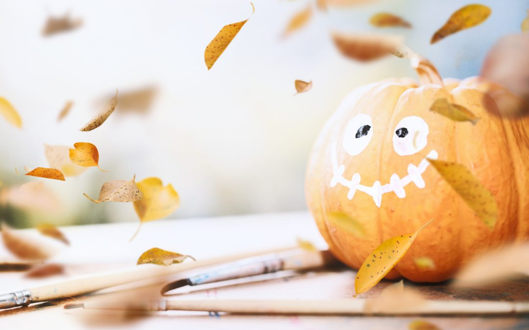 How to Paint a Pumpkin. Painted pumpkin smiling as leaves fall around him